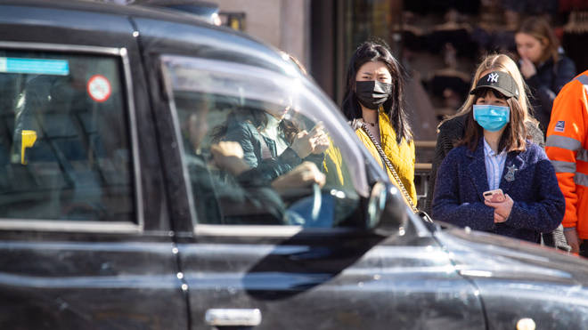 Two women in face masks on the streets of London