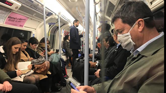 A man wears a coronavirus mask on the Tube