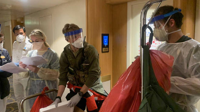 Medical personnel don protective equipment after delivering virus testing kits to the Grand Princess