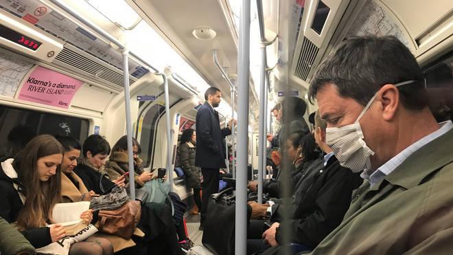 A man wears a coronavirus mask on the London underground