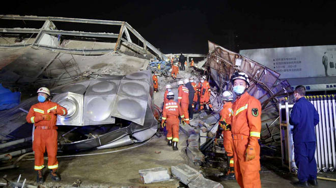 Rescuers work at the site of a collapsed five-story hotel building in Quanzhou city in southeast China's Fujian province
