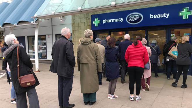 People queue outside a Boots pharmacy store in west London where stocks of hand sanitiser are limited to two per person