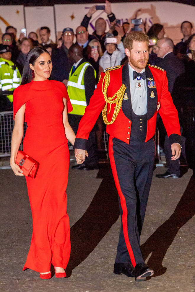 The duke wearing a Royal Marines officer's mess jacket and his wife wearing a red dress