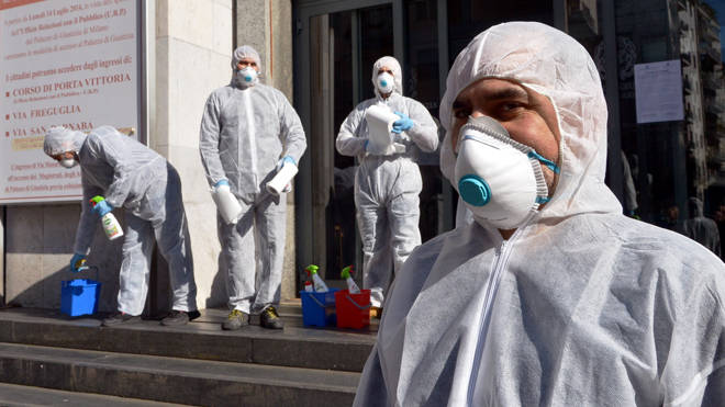 Workers carry out a coronavirus clean-up in Milan