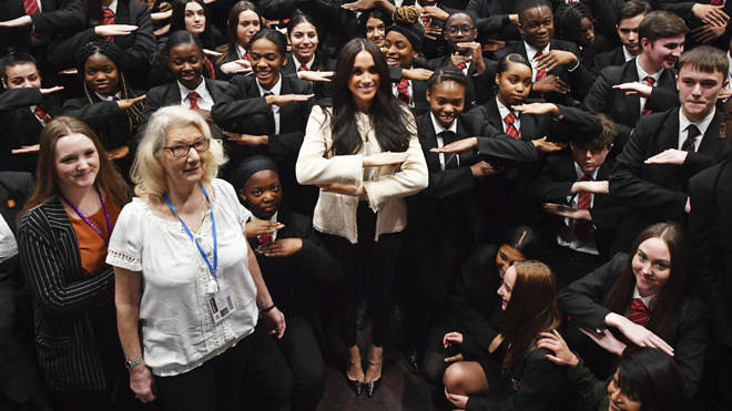 "Meghan makes the ""equality"" sign with schoolchilren"