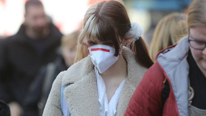 A woman wears a protective mask in a street in London