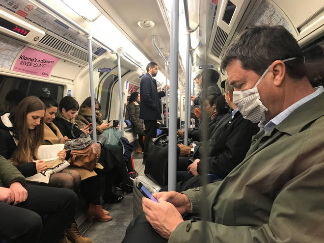 A London commuter wears an anti-Coronavirus mask