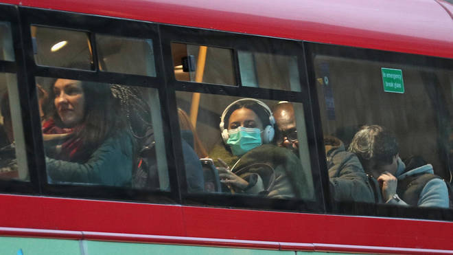 A woman in a protective mask on a London bus