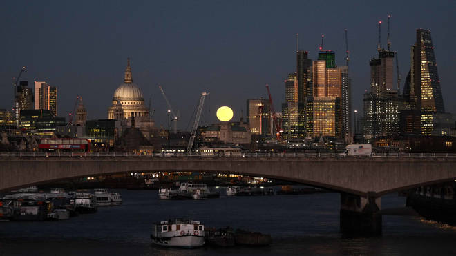 A blue super moon rises over the City of London