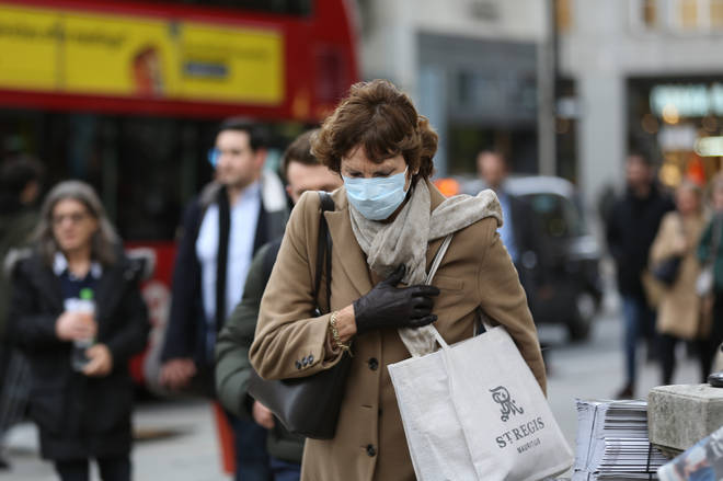 A woman in a protective mask walks in central London