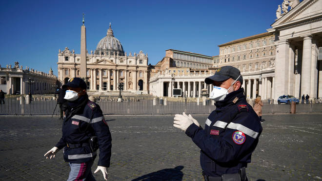Police officers wearing masks patrol an empty St. Peter's Square at the Vatican