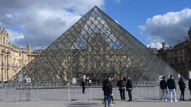 Tourists in front of the Musee du Louvre in Paris, undefinitely closed to the public amid concerns on the COVID-19 outbreak