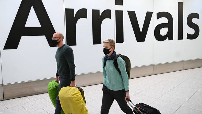 Passengers wear face masks as they arrive with their luggage at Terminal 4 of London Heathrow Airport in west London