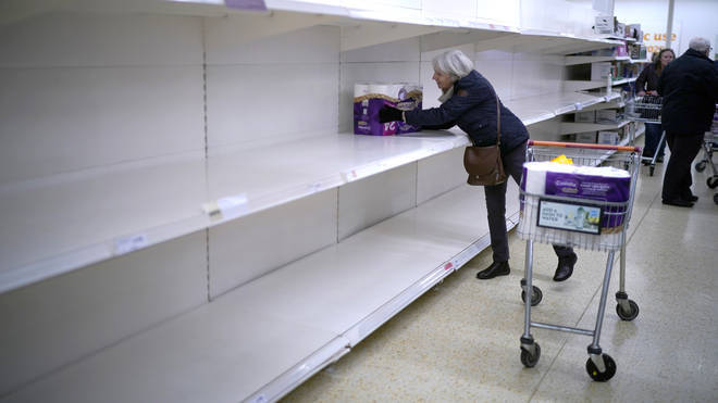 A woman gets the last pack of toilet rolls at Sainsbury's Supermarket on March 19, 2020 in Northwich