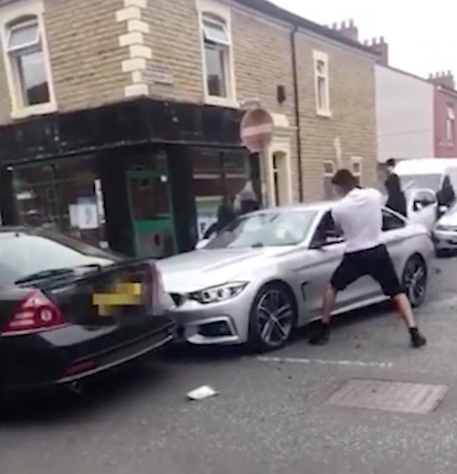 A group of men attack a BMW on a residential street
