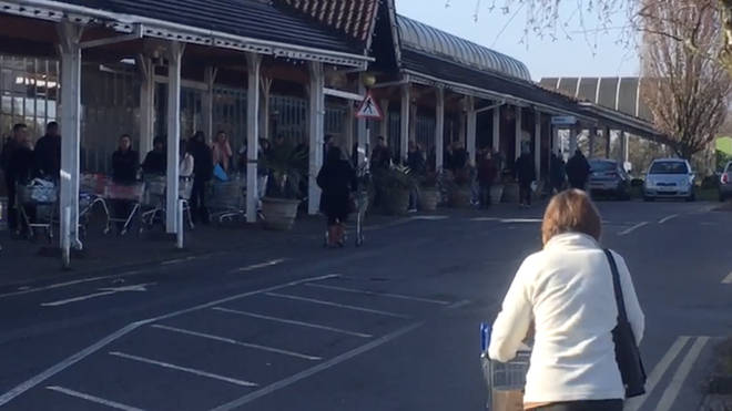 People queue out the shop at Shirley, West Mids, as they rush to buy food