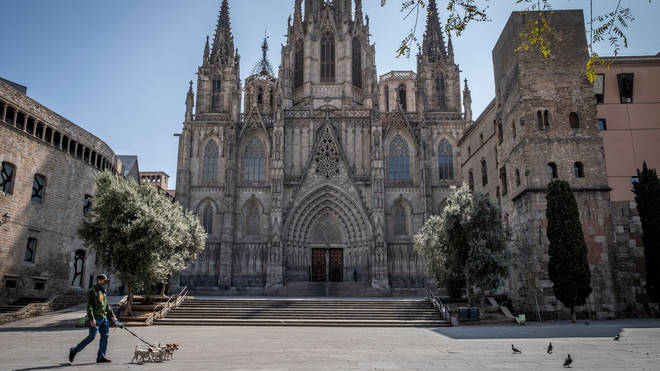 A man walking dogs past a deserted Cathedral of Barcelona during the period of confinement