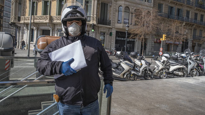 A delivery courier is seen wearing a mask in locked down Barcelona