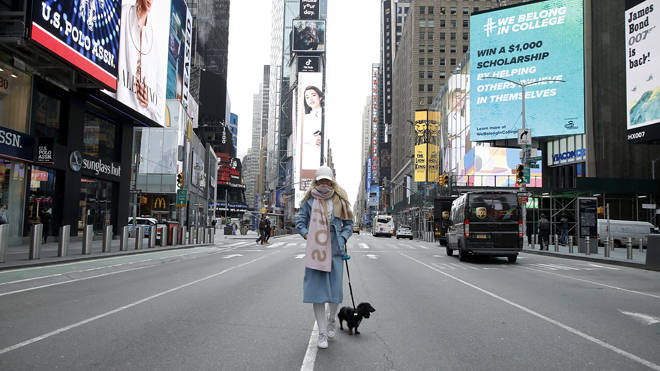 A woman stands in a virtually empty Time Square in New York