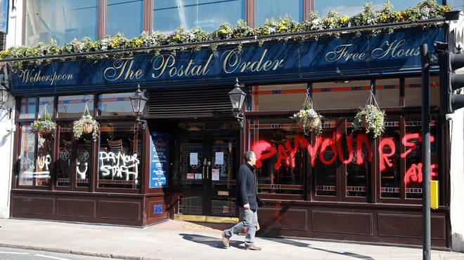 "Someone painted ""Pay Your Staff"" on the front of one of the pubs venues"