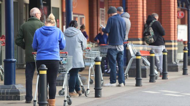 People queue 2 metres apart outside a supermarket