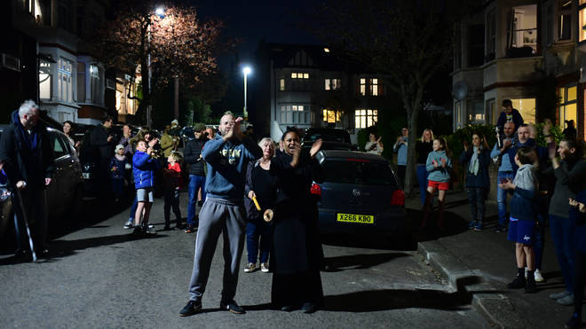 Residents of Woodford Green clap in their street