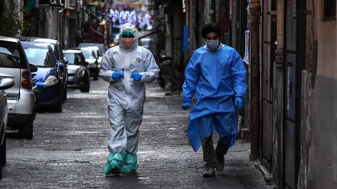 Doctors wear protective clothing as they carry out checks on citizens in Naples, Italy