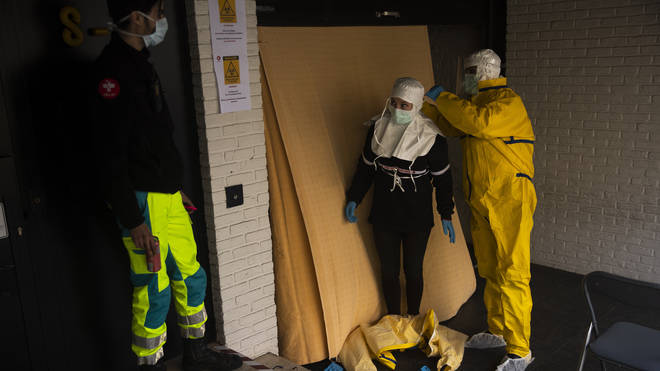 A 12-year-old girl has died of coronavirus in Belgium. Medical staff in the country are pictured helping each other with PPE