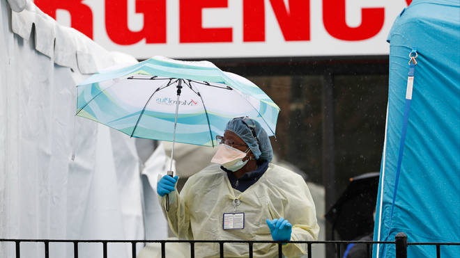 A medical worker holds an umbrella as she checks to to see if anyone is waiting in line outside a COVID-19 testing center at Elmhurst Hospital Center in New York