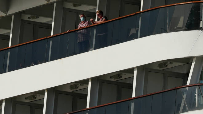 Passengers, one wearing a protective face mask, look out from the Zaandam cruise ship