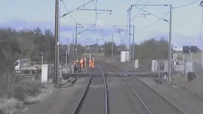 Workers scramble to safety as a train approaches