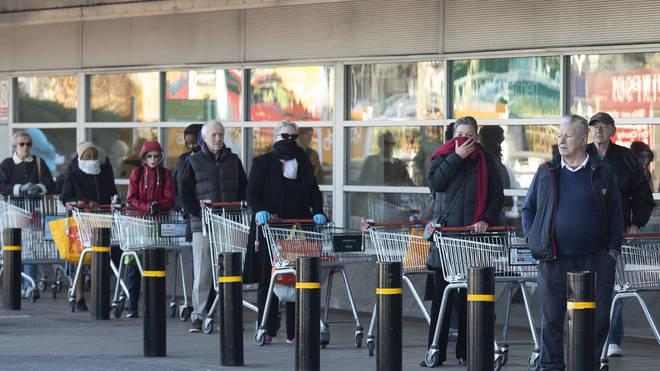 Shoppers queue outside a Sainsbury's supermarket
