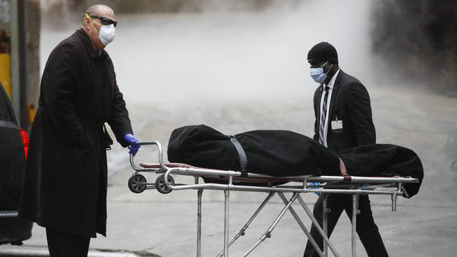 A funeral director wears personal protective equipment due to COVID-19 concerns while collecting a body at The Brooklyn Hospital Centre