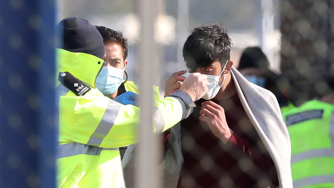 Border Force officers fit a mask to a suspected migrant
