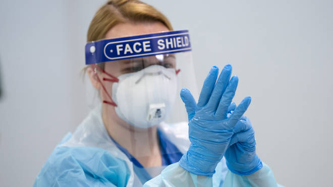 A member of staff receives training on how to put on and remove PPE, personal protective equipment (file image)