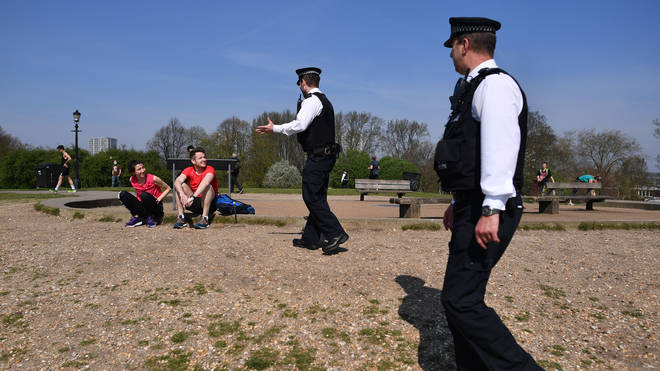 Police officers talk with a couple resting on Primrose Hill in London