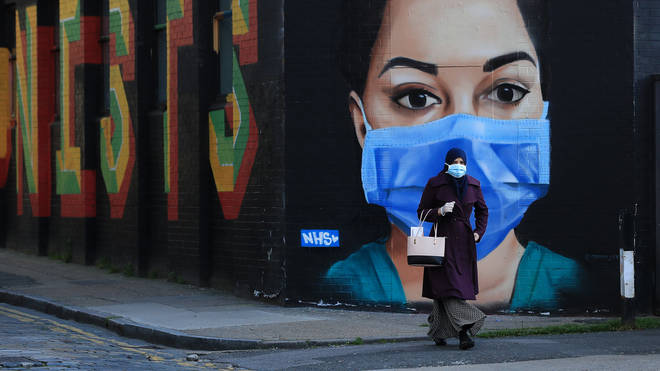 A woman wearing a face mask walks past a piece of street art depicting an NHS worker