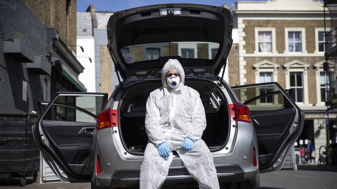 Uber driver Yasar Gorur wears personal protective equipment while cleaning his vehicle