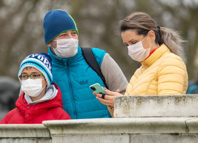 A family wear facemasks outside Buckingham Palace