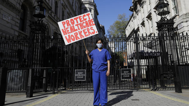 Doctor Meenal Viz holds a banner as she protests outside Downing Street in London, as the country is in lockdown to help curb the spread of the coronavirus,