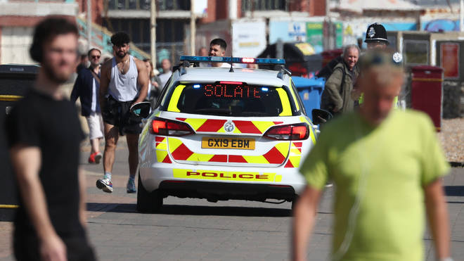 A police car patrols the promenade in Brighton as the UK continues in lockdown