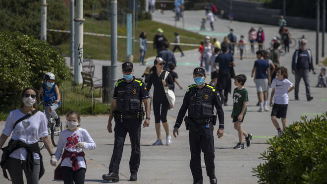 Catalan police officers patrol as families with their children walk along a boulevard in Barcelona