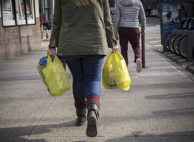 A shopper carries plastic bags