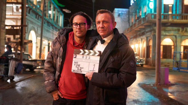 Daniel Craig (right) holding a signed clapperboard for No Time To Die, which went under the hammer to raise money for the NHS