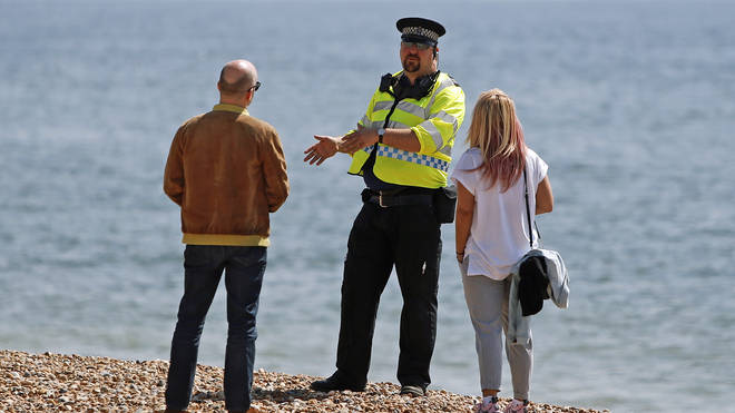 A police officer talks to a man and woman on Brighton beach