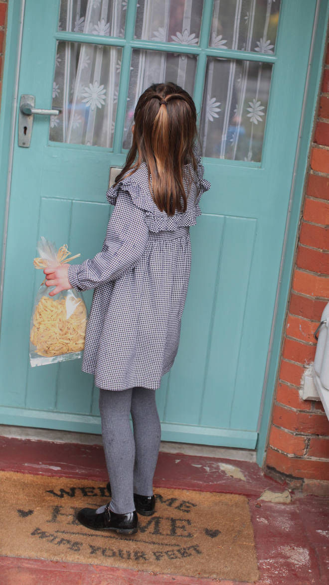 Charlotte knocks on the door of an elderly resident as she holds a bag of fresh pasta