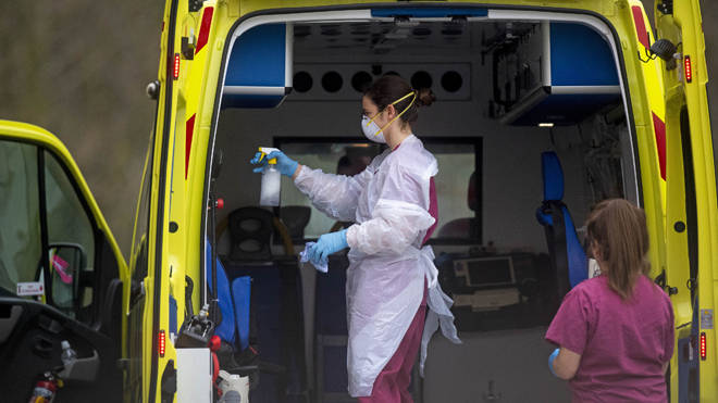 A London Ambulance worker wearing PPE cleans an ambulance after a patient is brought into St Thomas' Hospital in London