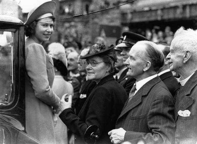 Princess Elizabeth (later Queen Elizabeth II) is greeted by crowds as she tours the East End of London on the day after VE Day