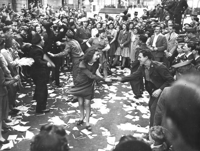 British girls, of the Picture Division of the London Office of War Information, dance in the street with American soldiers during the V-E Day celebrations
