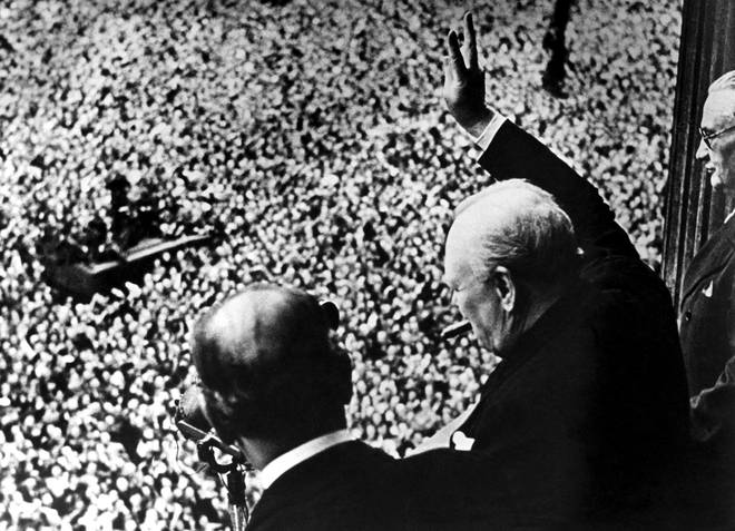 Winston Churchill gives his famous 'victory' salute a crowd of 50,000 full with the spirit of VE day from the balcony of the Ministry of Health,